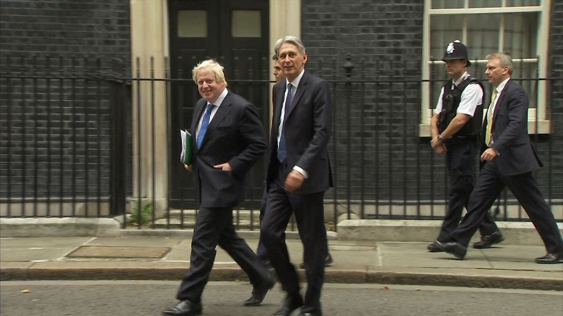 Boris Johnson and Philip Hammond walking together on Downing street.