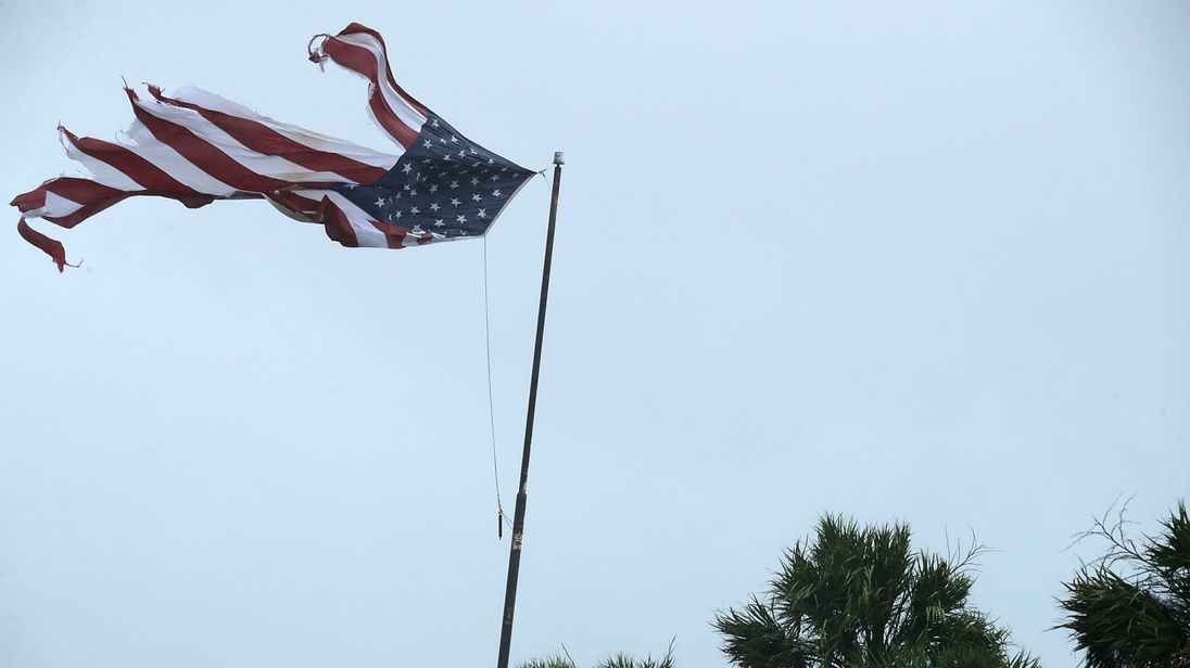 A US flag is tattered by strong winds from Hurricane Irma in Florida