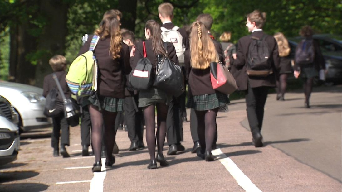 Group of schoolchildren (teenagers) walking in car park.