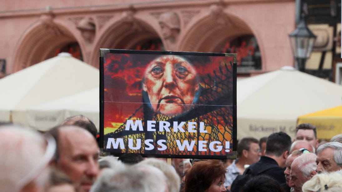 Protesters hold a sign reading 'Merkel must go'