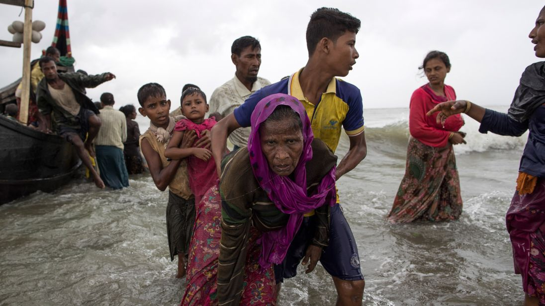 A Rohingya man helps an elderly woman out of the water after arriving in Dakhinpara, Bangladesh