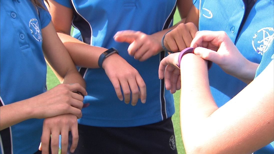 Children using exercise tracking devices at school