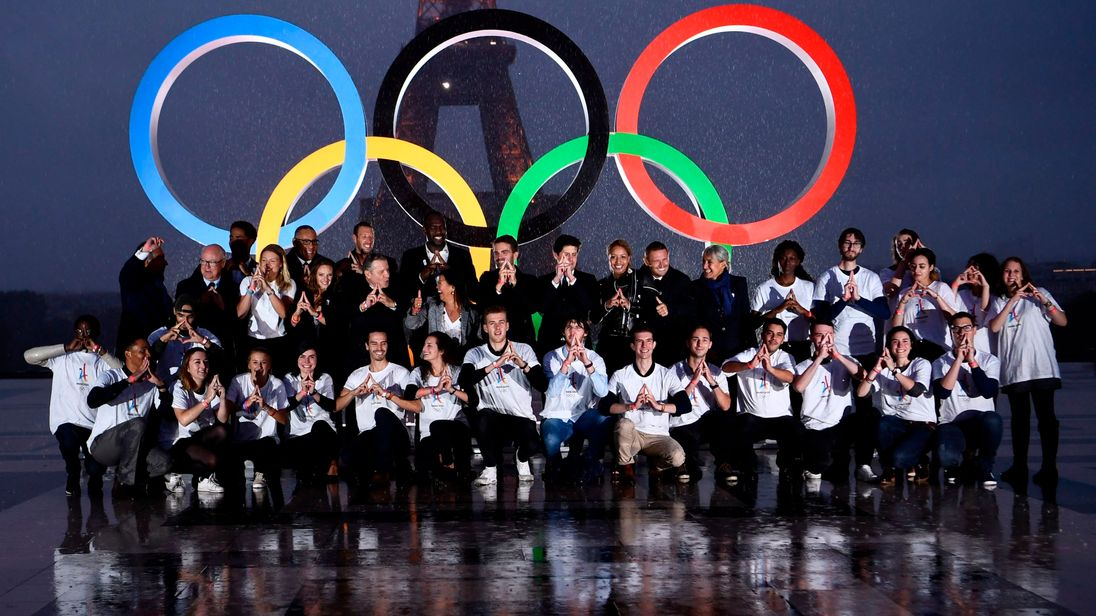 Volunteers pose in front of the Olympics Rings on the Trocadero Esplanade near the Eiffel Tower in Paris, on September 13, 2017, after the International Olympic Committee named Paris host city of the 2024 Summer Olympic Games. The International Olympic Committee named Paris and Los Angeles as hosts for the 2024 and 2028 Olympics on September 13, 2017, crowning two cities at the same time in a historic first for the embattled sports body.