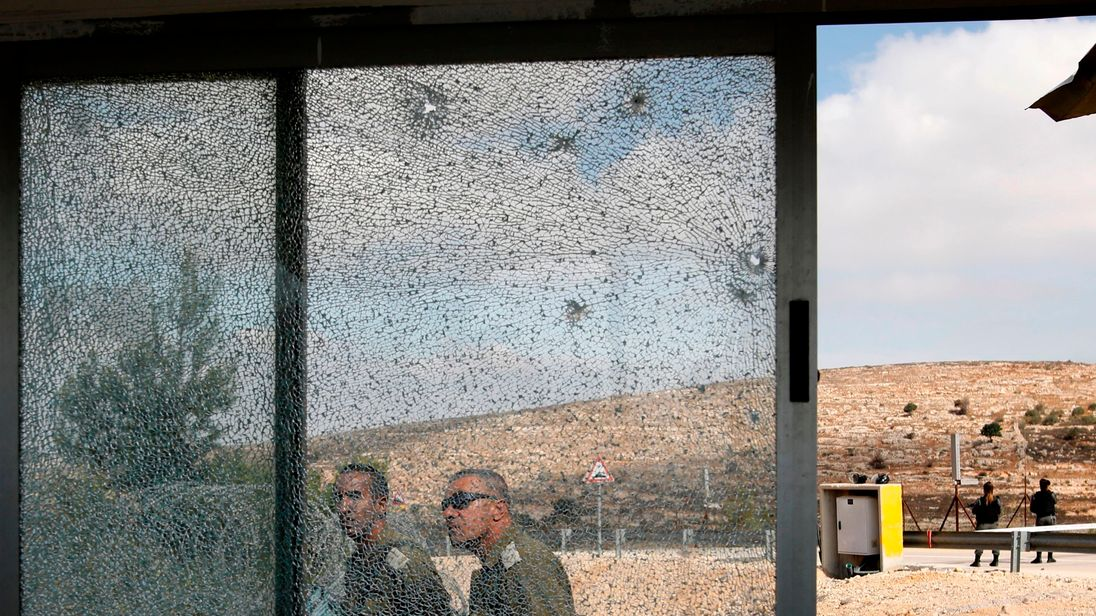 TOPSHOT - Members of the Israeli security forces walk past the shattered glass of the security post at the entrance to the West Bank settlement of Har Adar after a Palestinian opened fire on security personnel in a fatal attack before being shot dead on September 26, 2017. / AFP PHOTO / Menahem KAHANA (Photo credit should read MENAHEM KAHANA/AFP/Getty Images)