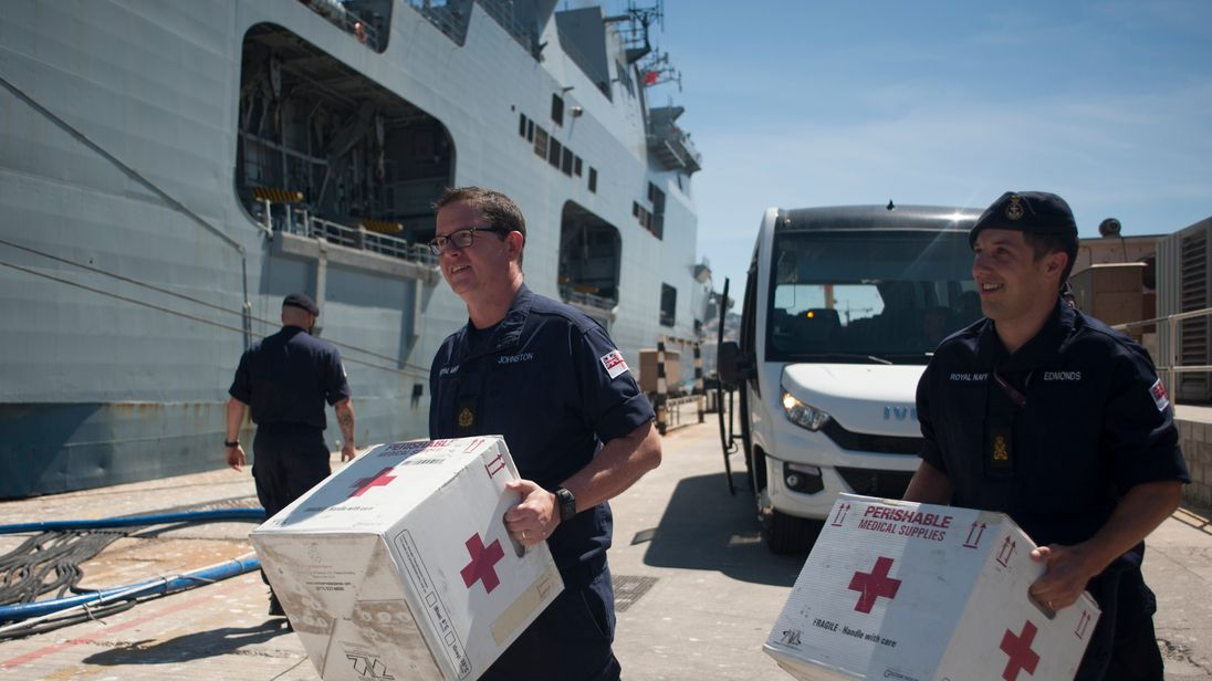 Members of the Royal Navy carry medical supplies on board the amphibious assault ship HMS Ocean at the Naval Base in Gibraltar on September 11, 2017, before leaving to provide humanitarian assistance and vital aid to British Overseas Territories and Commonwealth partners affected by Hurricane Irma.