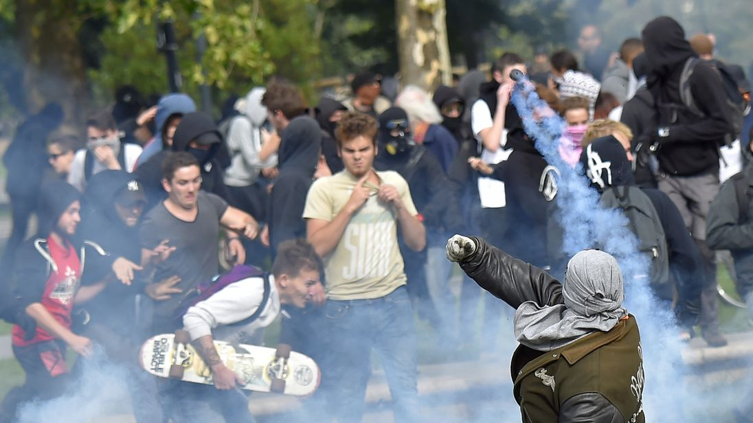 A protester (R) throws back a tear gas canister in Nantes