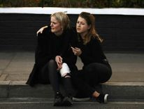 An injured woman reacts outside Parsons Green tube station
