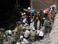 A rescue worker motions for everybody to be quiet as they search for people under the rubble