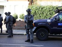 Armed policemen stand by cordon outside Parsons Green tube station in London