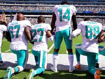Laremy Tunsil #67, Maurice Smith #27 and Julius Thomas #89 kneel with Jarvis Landry #14