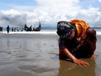 An exhausted Rohingya refugee woman touches the shore after crossing the Bangladesh-Myanmar border by boat through the Bay of Bengal