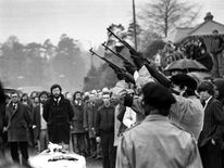 May 1981: Three masked IRA men fire volleys of rifle shots over the coffin of hunger-striker Bobby Sands. Belfast. Gerry Adams can be seen in background