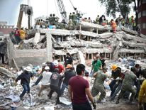 Rescuers, firefighters, policemen, soldiers and volunteers search for survivors in a flattened building