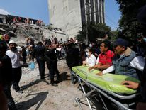 Paramedics wait as rescue personnel search for people in the rubble