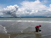 Smoke is seen on Myanmar's side of border as a Rohingya refugee woman cleans her shoes after crossing the Bangladesh-Myanmar border