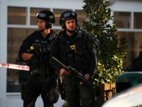 Armed policemen stand by a cordon