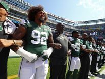 The New York Jets stands in unison during the US National Anthem prior to an NFL game against the Miami Dolphins