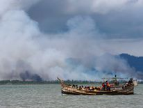 Smoke is seen on Myanmar's side of border as a boat carrying Rohingya refugees arrives on shore after crossing the Bay of Bengal
