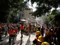 A man motions for everybody to be quiet as rescue workers look for people under the rubble