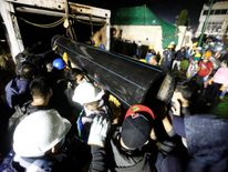 Workers carry a tube during the search for students at Enrique Rebsamen school