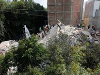 Rescue workers look for people under the rubble