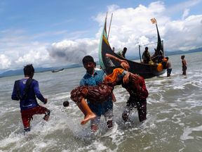 Smoke is seen on the border as a Rohingya refugee is carried to the shore after escaping Myanmar
