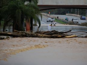 People wade through a flooded expressway in Yauco, Puerto Rico