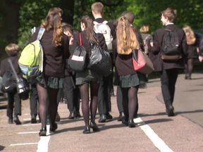 Group of schoolchildren (teenagers) walking in car park.