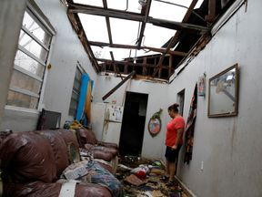 A woman looks at the damages in the neighbour's house after the area was hit by Hurricane Maria in Salinas, Puerto Rico, September 21, 2017