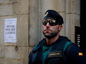 Guardia Civil stands next to a pro-referendum poster reading 'Vote to be free' in Catalan