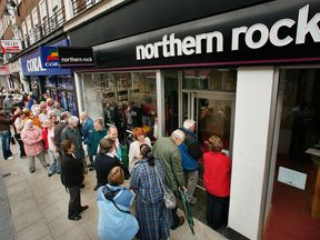 Customers wait in line to remove their savings from a branch of The Northern Rock bank on September 17, 2007 in Kingston-Upon-Thames, England