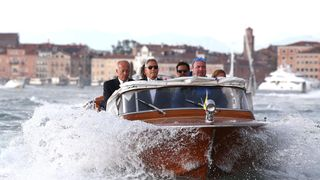 Actor and director George Clooney rides on a taxi boat