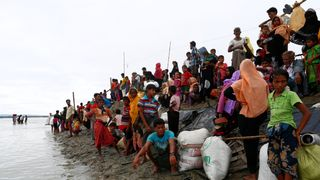 Rohingya refugees wait at a jetty after crossing the Bangladesh-Myanmar border by boat through the Bay of Bengal in Shah Porir Dwip
