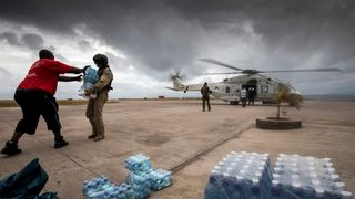 Dutch Army soldiers unload bottles of drinking water at the Sint Maarten International Airport on Saint Martin Island