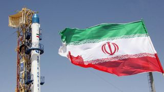 A picture taken on August 16, 2008 shows A picture taken on August 16, 2008 shows an Iranian flag fluttering in front of Iran's Safir Omid rocket, which is capable of carrying a satellite into orbit, before it's launch in a space station at an undisclosed location in the Islamic republic. Iran said on August 17 it had successfully launched the rocket, a move that could further exacerbate tensions with the West over its nuclear drive. AFP PHOTO/STR/VAHIDREZA ALAI (Photo credit should read VAHIDRE
