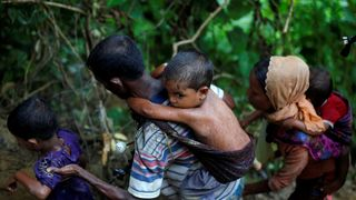 Rohingya refugees climb up a hill after crossing the Bangladesh-Myanmar border in Cox's Bazar
