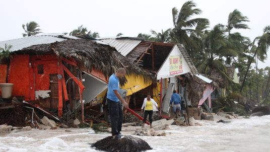 People walk among debris on the seashore in the aftermath of Hurricane Maria in Punta Cana, Dominican Republic