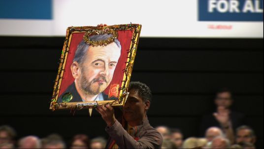 A delegate at Labour conference holds up a portrait of Jeremy Corbyn. Still from 11:50 on conference floor