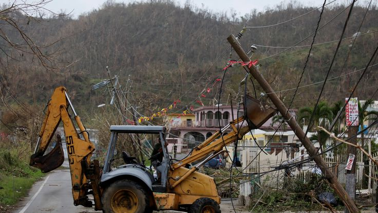A worker removes damaged power lines in Yabucoa, Puerto Rico