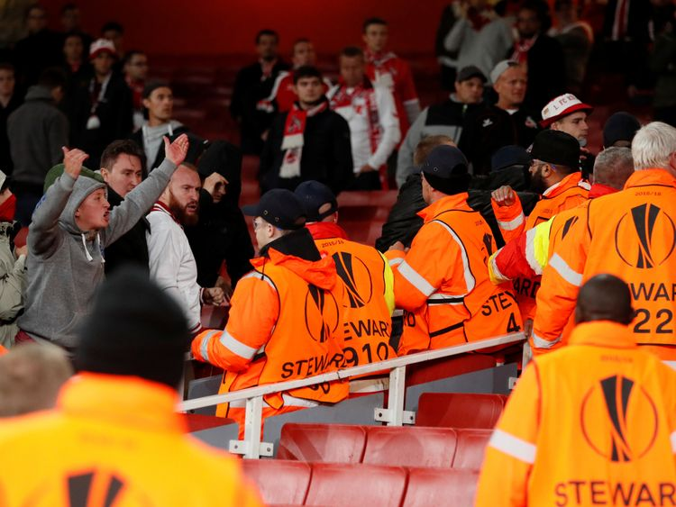 FC Koln fans square up to stewards inside the stadium before the delayed match
