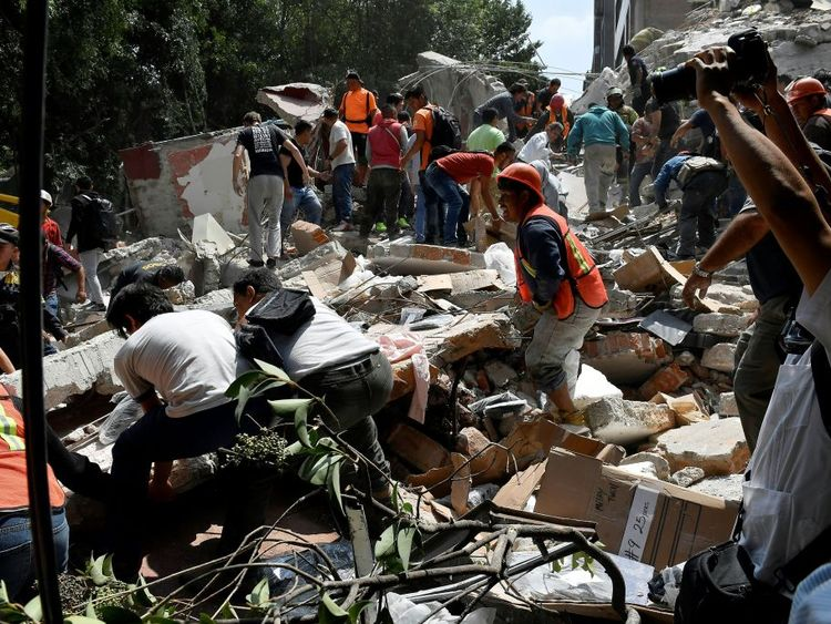 Rescuers frantically try to move rubble after the 7.1 magnitude quake