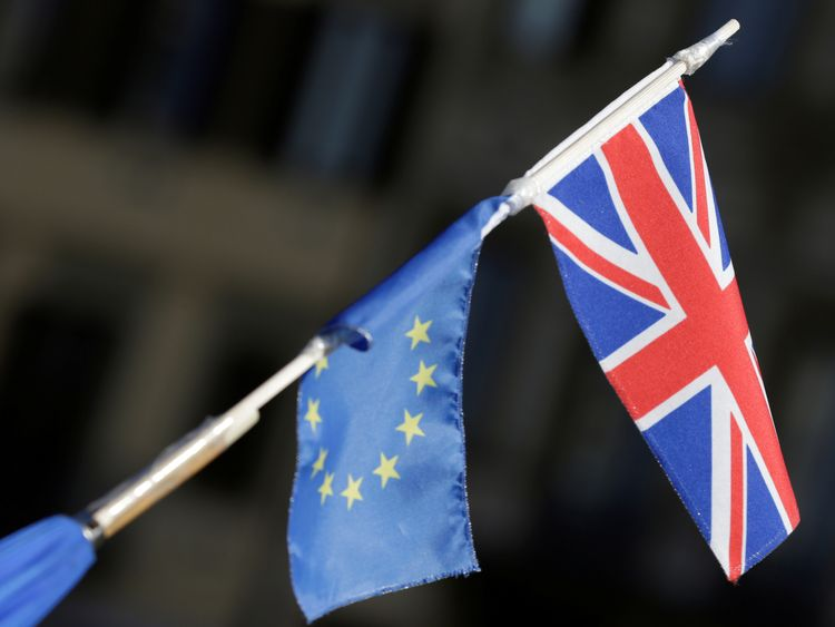 An umbrella with EU and British flags attached to it is held ahead of a speech by Britain's Prime Minister
