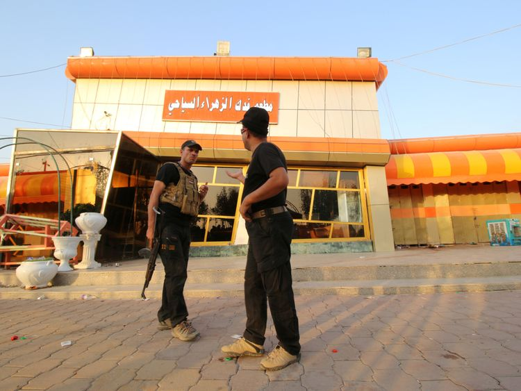 Iraqi security forces inspect the site of a bomb attack in a restaurant