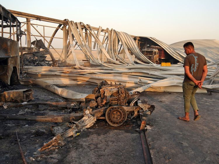 An man looks at the damage after gunmen and suicide car bombers killed dozens of people