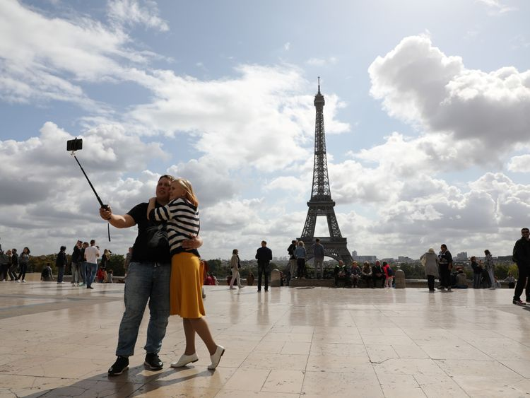 A couple take a selfie in front of the Eiffel tower in Paris