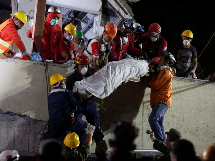 Rescue workers remove a dead body after searching through rubble at Enrique Rebsamen school