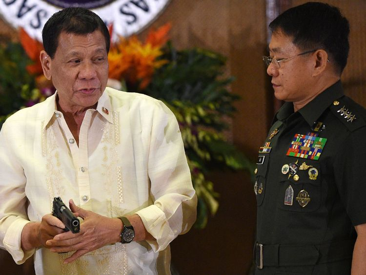 Philippine President Rodrigo Duterte (L) holds a handgun as military chief Eduardo Ano (R) looks on in July 2017