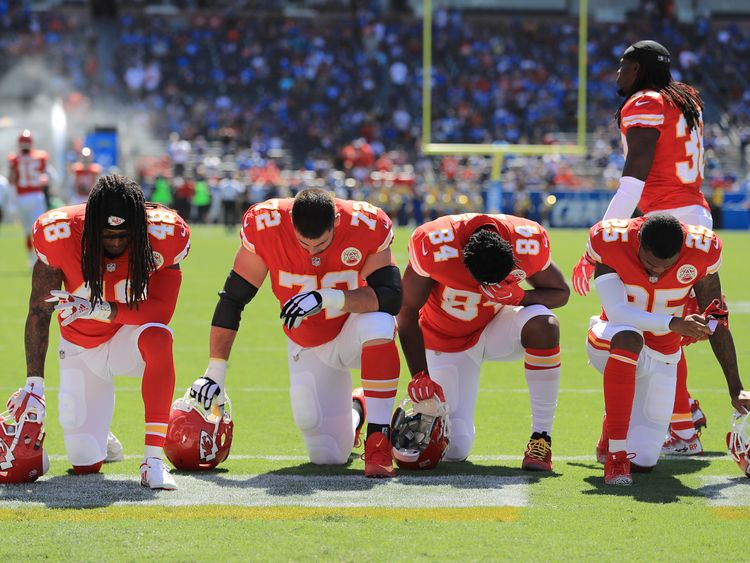 Terrance Smith #48, Eric Fisher #72, Demetrius Harris #84, and Cameron Erving #75 of the Kansas City Chiefs is seen taking a knee