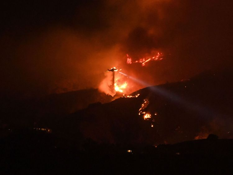 A helicopter drops water on the La Tuna Canyon fire at night in the hills above Burbank, California, early September 2, 2017. The brush fire which quickly burned 2,000 acres started on September 1 and was being driven by heat wave temperatures and high winds