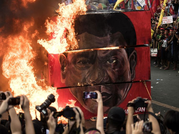 Activists burn an effigy during a protest against Rodrigo Duterte in Manila